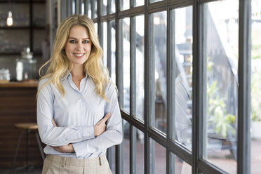 portrait of attractive business woman in office in front of windows - SBOF01606