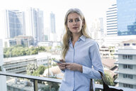 Blond woman with smartphone leaning agianst glass railing in the city - SBOF01609