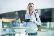 Blond woman with tablet standing at glass railing in the city - SBOF01612