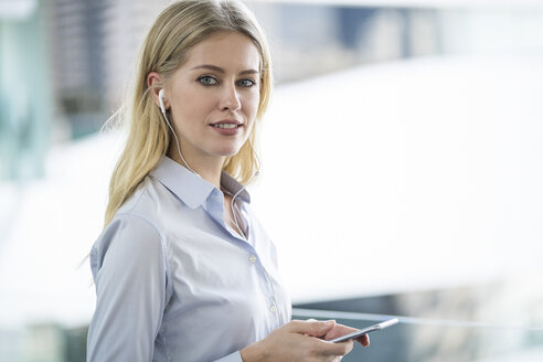 Portrait of blond woman with smartphone and earphones - SBOF01615