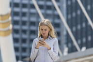 Blond woman with handbag checking cell phone in the city - SBOF01618