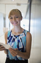 Portrait smiling businesswoman with digital tablet in office corridor - HEROF05671