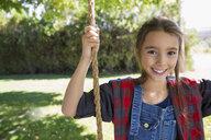 Portrait smiling girl swinging on swing in summer yard - HEROF05692