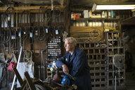 Pensive senior male mechanic looking away in workshop - HEROF05707