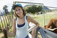 Portrait smiling female farmer with pitchfork on sunny cattle farm - HEROF05722