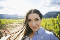 Portrait smiling brunette woman in sunny vineyard - HEROF05758