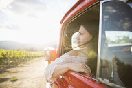 Pensive woman riding in truck in sunny vineyard - HEROF05761