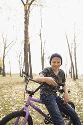 Portrait smiling boy tween boy with bicycle in autumn park - HEROF05797