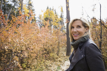 Portrait smiling blonde woman walking in autumn woods - HEROF05809