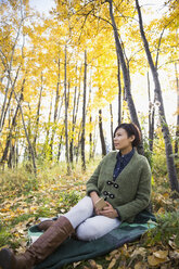 Pensive woman with cell phone relaxing on blanket in autumn woods - HEROF05821