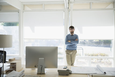 Portrait confident male architect with arms crossed at office window - HEROF05854