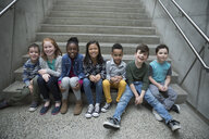 Portrait smiling children sitting in a row on stairs - HEROF05866