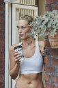 Sporty young woman with takeaway drink at house entrance - RORF01569