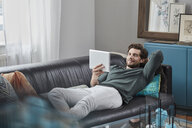 Smiling man with tablet lying on couch at home - RORF01572