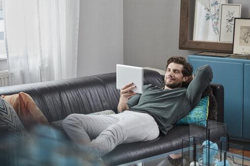 Deutschland, Nordrhein-Westfalen, Stadt Essen, Familie, Lifestyle, Mann mit Tabletcomputer auf dem Sofa, Internet-Shopping, Online-Banking, Wohnzimmer - RORF01572