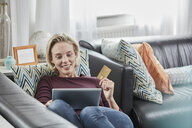 Happy woman with tablet and credit card lying on couch at home - RORF01584