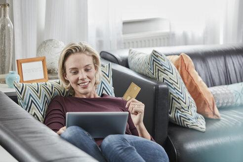 Deutschland, Nordrhein-Westfalen, Stadt Essen, Familie, Lifestyle, Frau mit Tabletcomputer, Kreditkarte, Internet-Shopping, Online-Banking, Sofa, Wohnzimmer - RORF01584