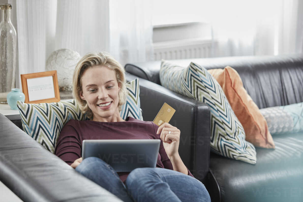 Happy woman with tablet and credit card lying on couch at home - RORF01584 - Roger Richter/Westend61