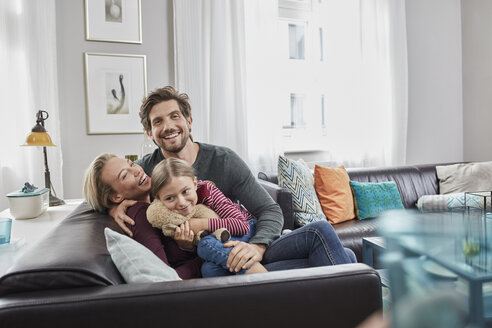 Portrait of happy family sitting on couch at home - RORF01587