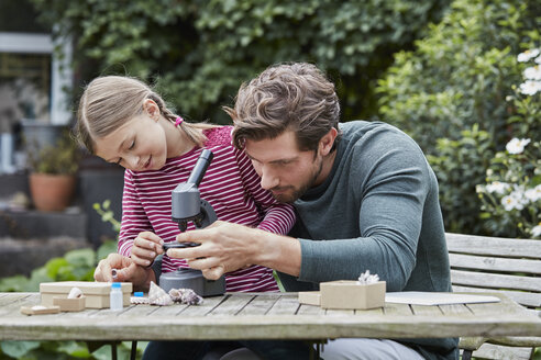 Father and daughter using microscope together at garden table - RORF01608