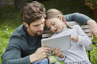 Father and daughter using tablet together in garden - RORF01611