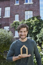 Portrait of smiling man in front of his home holding house model - RORF01614