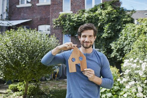 Deutschland, Nordrhein-Westfalen, Stadt Essen, Familie, Lifestyle, Mann vor Backsteinhaus mit Immobilien-Model, Haus, Immobilie - RORF01617