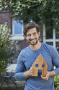 Portrait of smiling man in front of his home holding house model - RORF01620