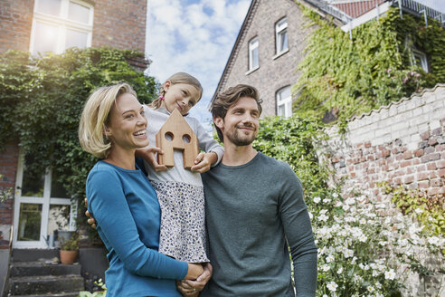 Portrait of happy family in front of their home with house model - RORF01623