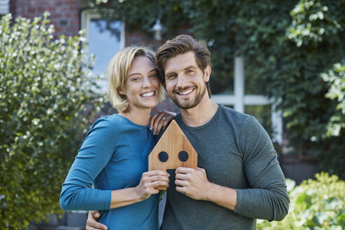 Portrait of happy couple in front of their home with house model - RORF01626