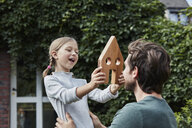 Father and daughter in garden of their home with house model - RORF01629
