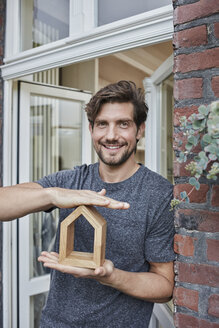 Portrait of smiling man at house entrance holding house model - RORF01635