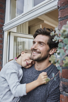 Smiling father with daughter at house entrance of their home - RORF01638