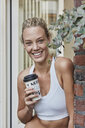 Portrait of smiling sporty young woman with takeaway drink at house entrance - RORF01644