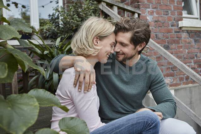 Happy couple sitting on stairs cuddling - RORF01650
