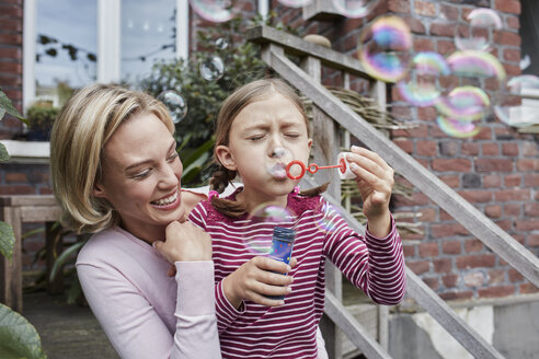 Happy mother and daughter making soap bubbles - RORF01653