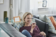 Smiling young woman using cell phone lying on couch at home - RORF01656