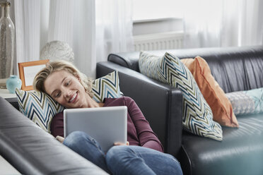 Smiling young woman with tablet lying on couch at home - RORF01659