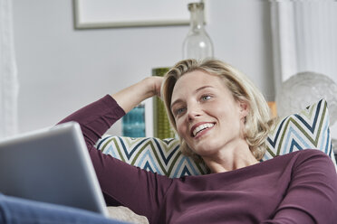 Smiling young woman with tablet lying on couch at home - RORF01662