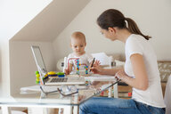 Mother using laptop and little daughter playing at table at home - DIGF05614