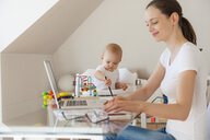Smiling mother using laptop and little daughter playing at table at home - DIGF05617