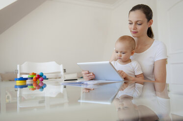 Mother and little daughter using tablet together at home - DIGF05632