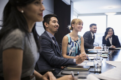Smiling business people listening in conference room meeting - HEROF05895