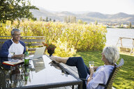Retired couple relaxing drinking wine and using laptop at lakeside patio - HEROF05937