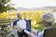 Retired couple using digital tablet and drinking white wine at patio table - HEROF05940