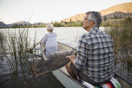Retired couple canoeing on tranquil lake - HEROF05949