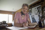 Portrait smiling senior woman artist sketching in notebook in art studio - HEROF06018