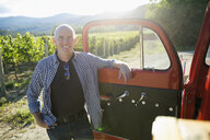 Portrait smiling vintner at truck door in sunny vineyard - HEROF06027