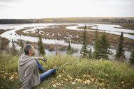 Serene man with binoculars looking at autumn lake view - HEROF06069
