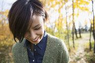 Smiling brunette woman looking down in autumn woods - HEROF06078
